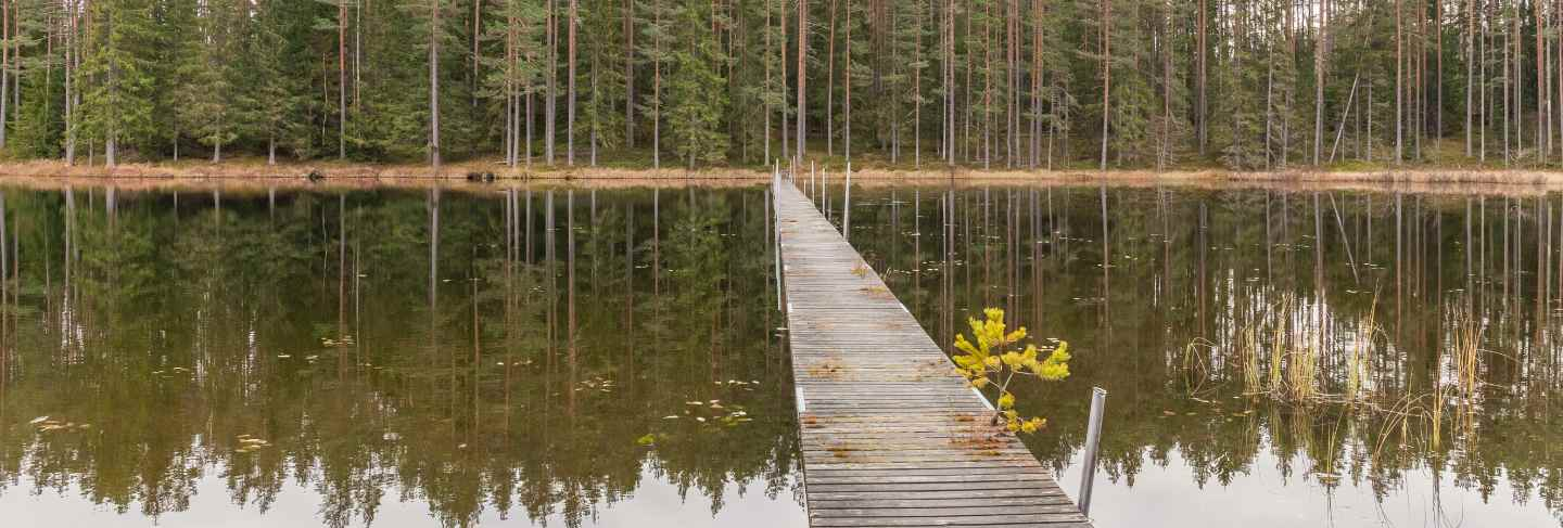 Wooden pier leading to the opposite shore, autumn landscape. sweden.