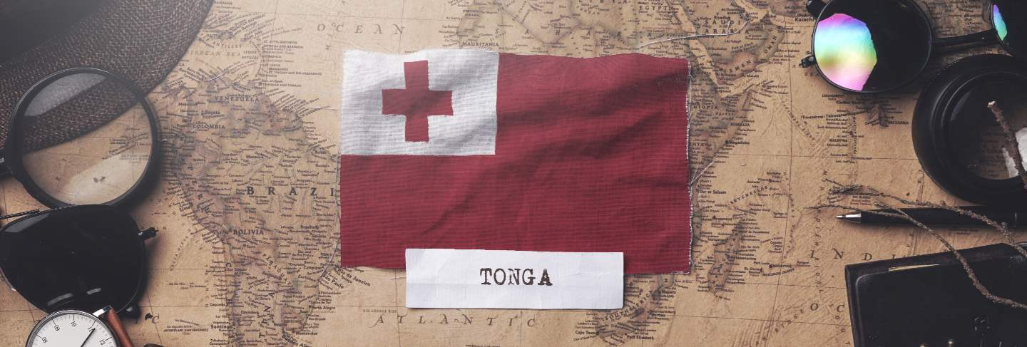 Tonga flag between traveler's accessories on old vintage map.