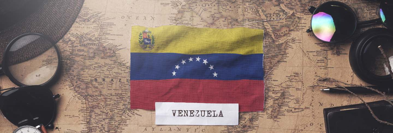 Venezuela flag between traveler's accessories on old vintage map. overhead shot