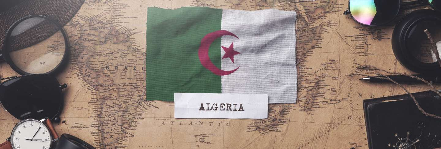 Algeria flag between traveler's accessories on old vintage map.