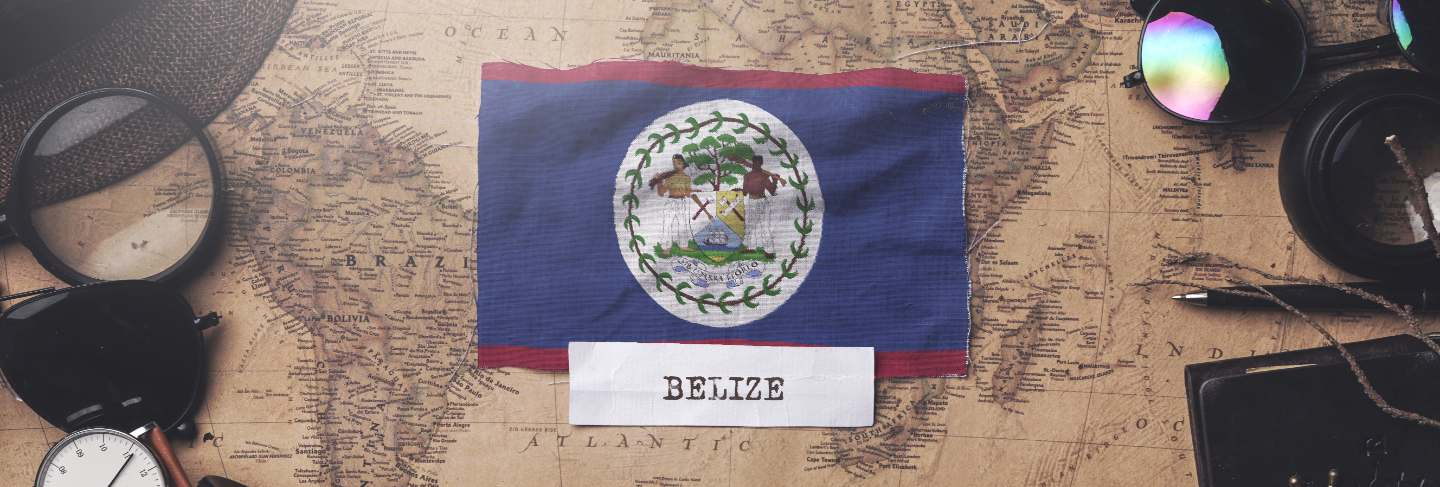 Belize flag between traveler's accessories on old vintage map.
