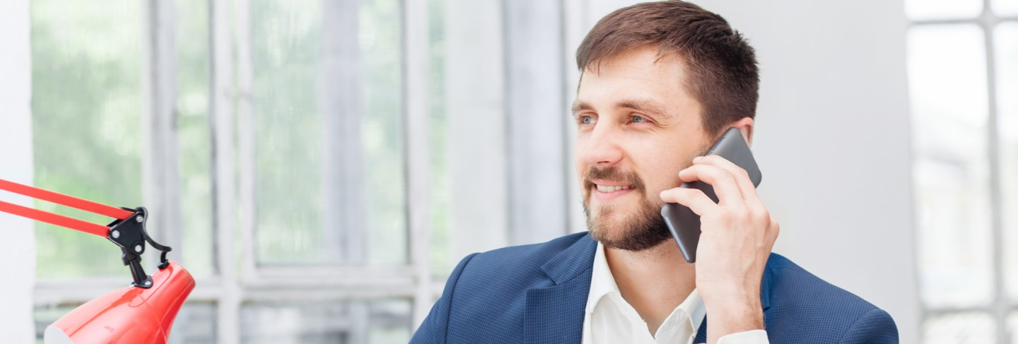 Portrait of businessman talking on phone in office