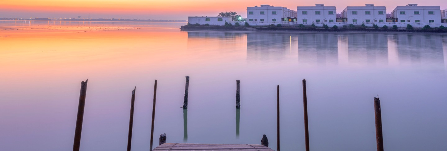 Wooden bridge out on the water over sunrise colorful sky with traditional local house in the island background,