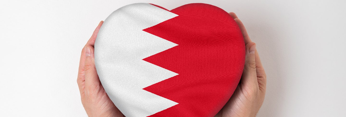 Flag of bahrain on a heart shaped box in a male hands.