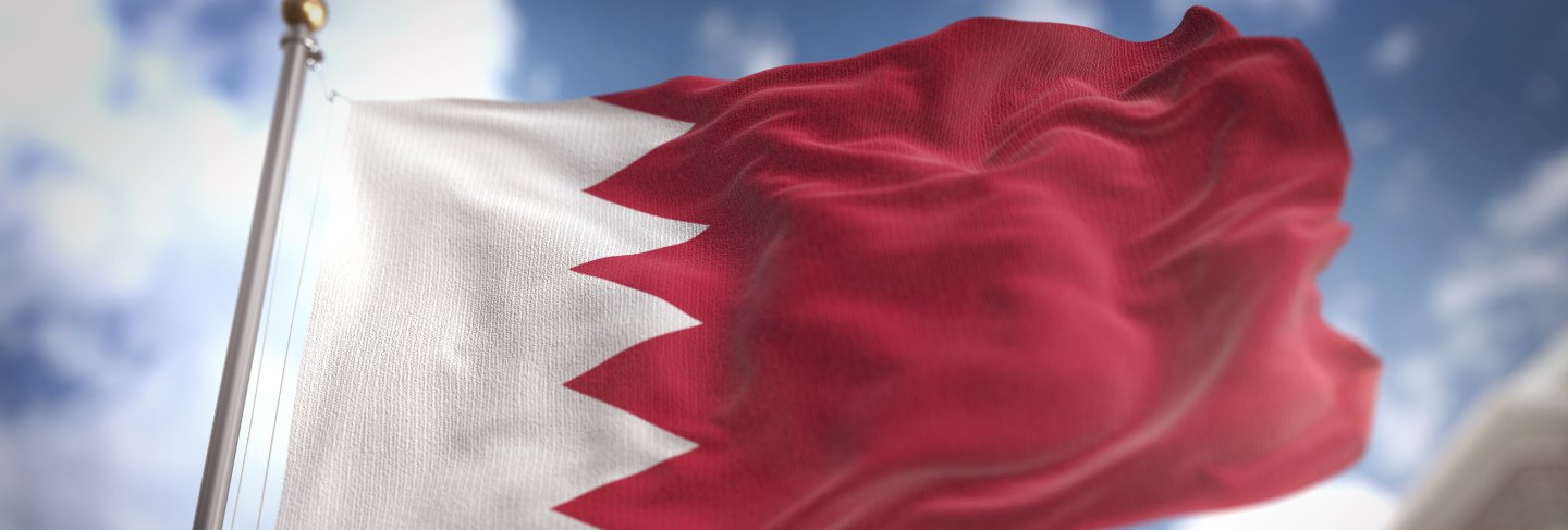 Bahrain flag 3d rendering on blue sky building background
