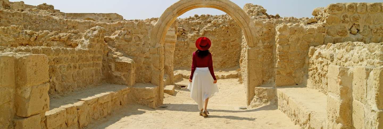 Woman admiring the bahrain fort or qal'at al-bahrain in manama, bahrain