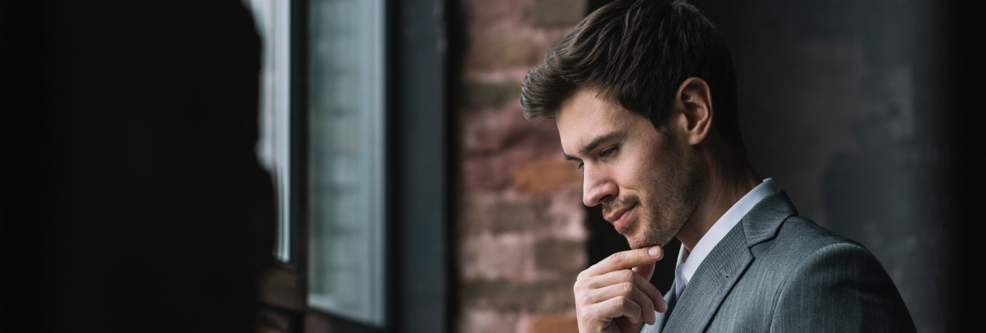 Thoughtful smart young businessman looking at laptop