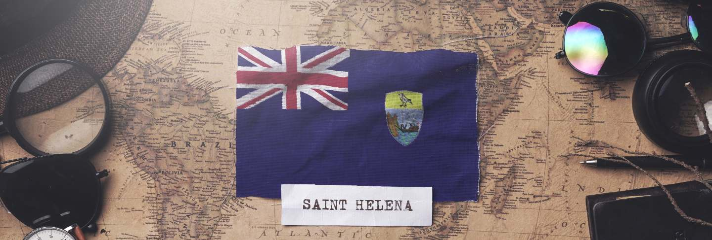 Saint helena flag between traveler's accessories on old vintage map.