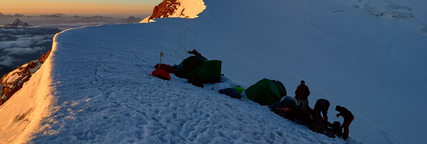 Group alpinists in base camp on snowy peak places tent at sunset, tajikistan