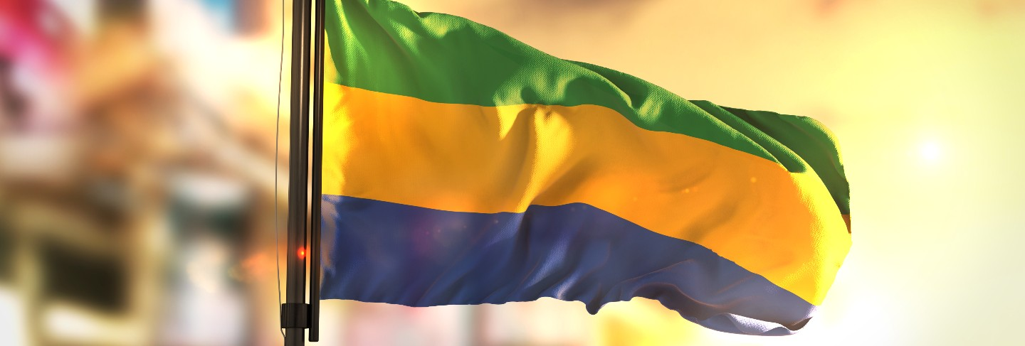 Gabon flag against city blurred background at sunrise
