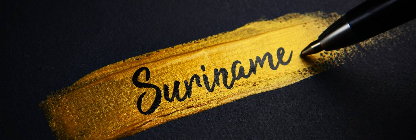 Suriname handwriting text on golden paint brush stroke