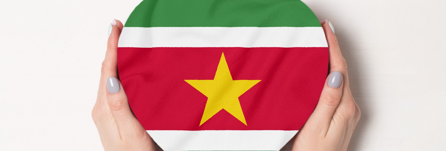 Flag of suriname on a heart shaped box in a female hands