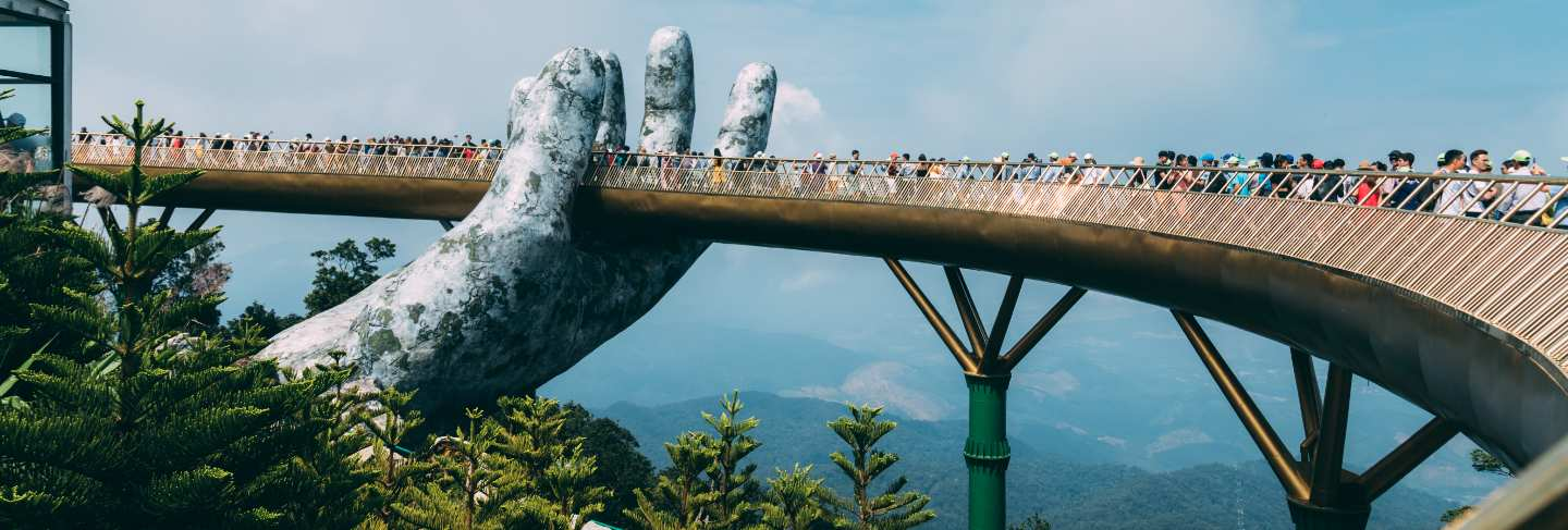 The golden bridge is lifted by two giant hands in the tourist resort on ba na hill in danang, vietnam. ba na hill mountain resort is a favorite destination for tourists of central vietnam