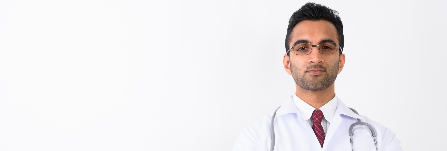 Young handsome indian man doctor against white background