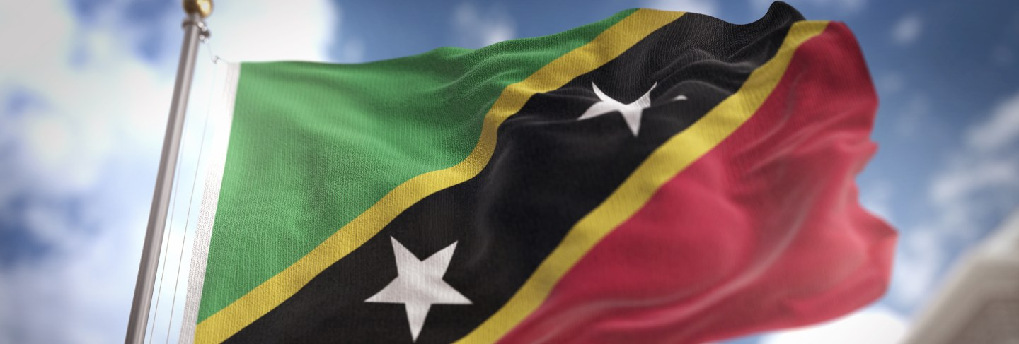 Flag of saint kitts and nevis on a heart shaped box in a female hands.