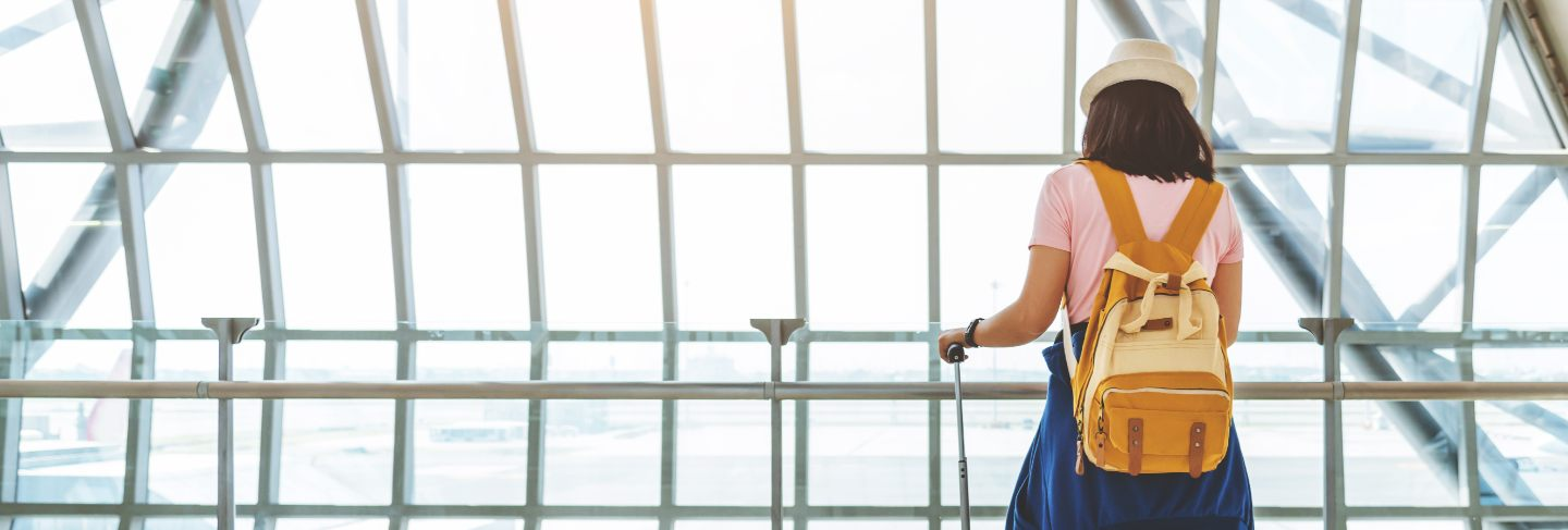 Asian young woman with suitcase and yellow backpack waiting for the flight at window of the airport