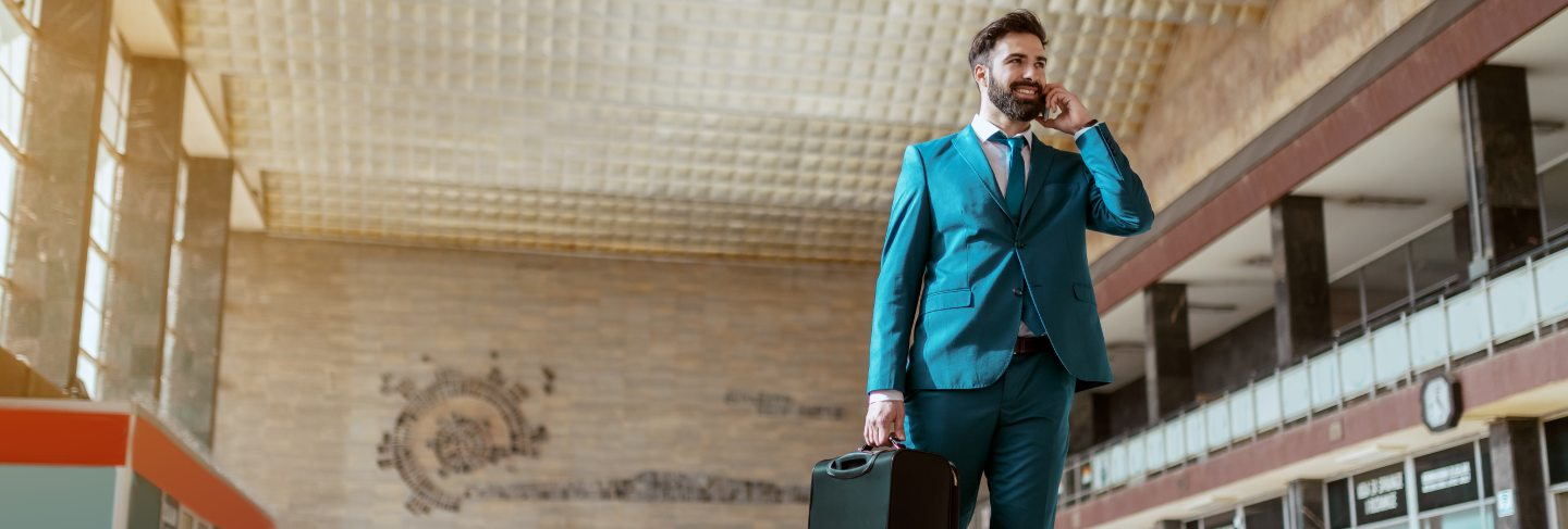 Young attractive bearded smiling businessman in blue suit carrying luggage and using smart phone while standing at train station. business trip concept