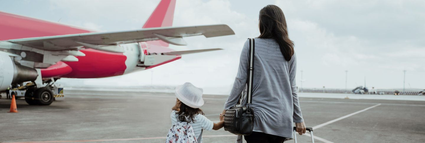 Little girl and mother holding hands walk towards the plane