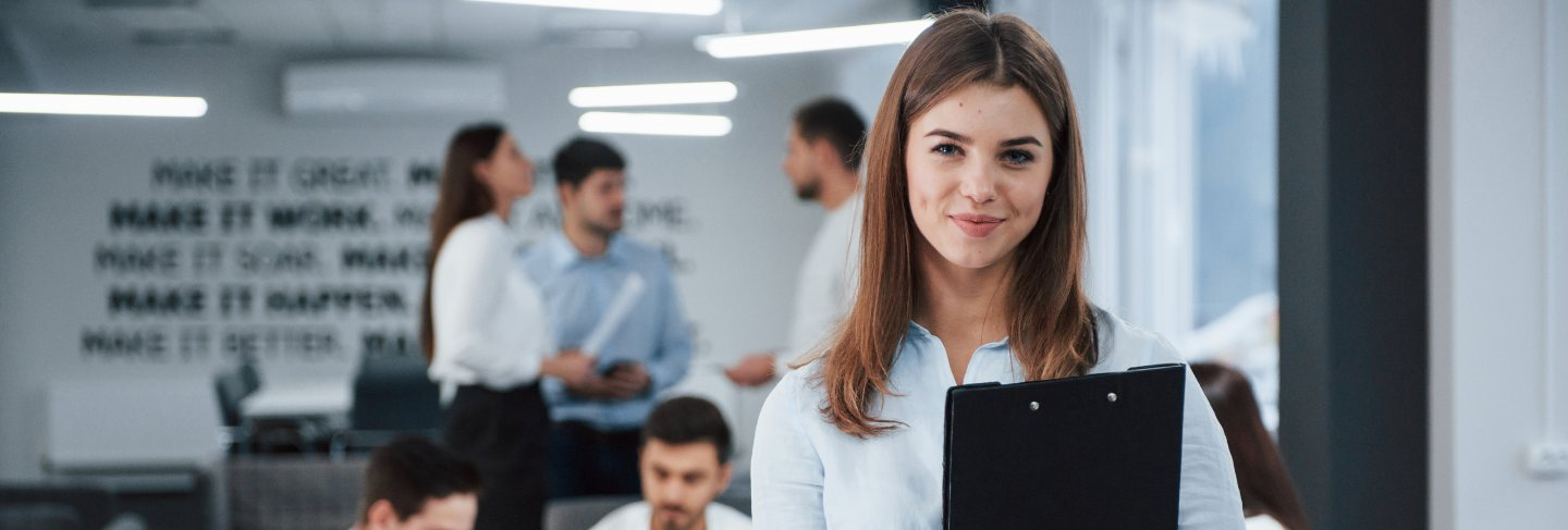Conception of success. portrait of young girl stands in the office with employees