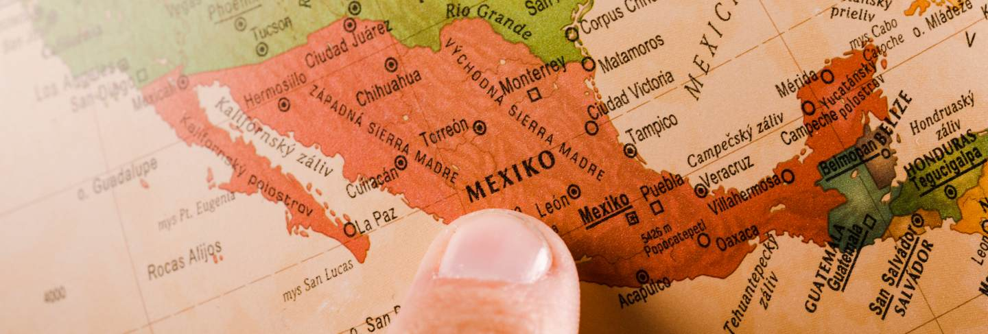 A person's finger showing mexico city on map