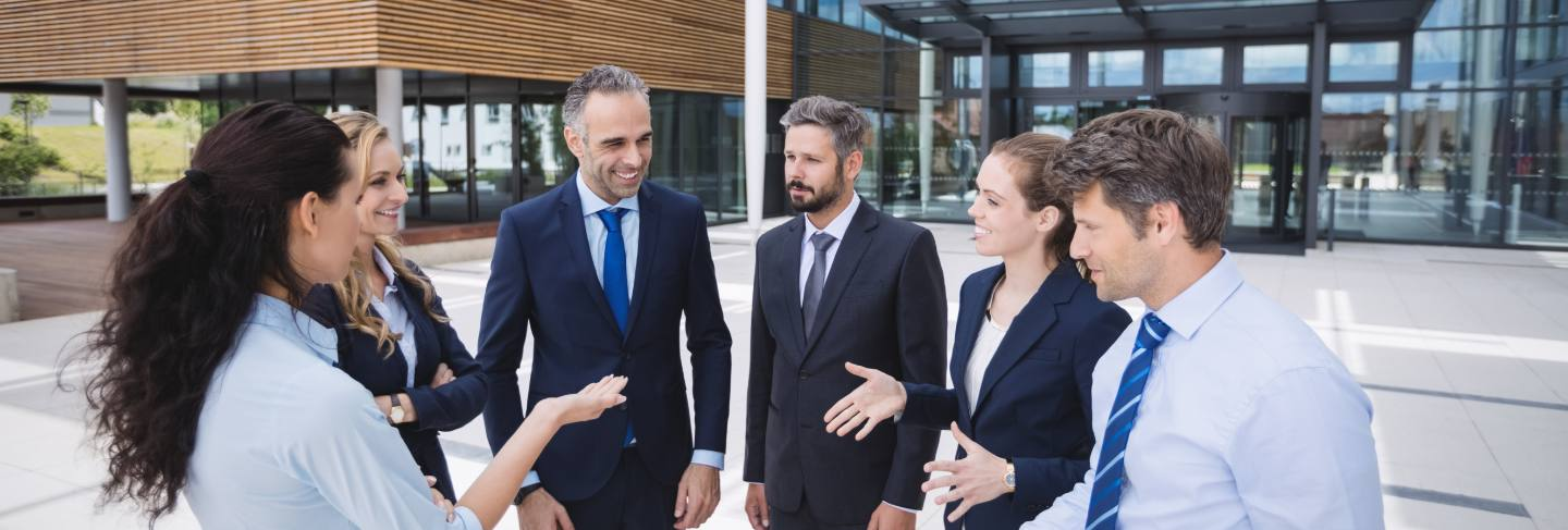 Group of businesspeople interacting outside office building