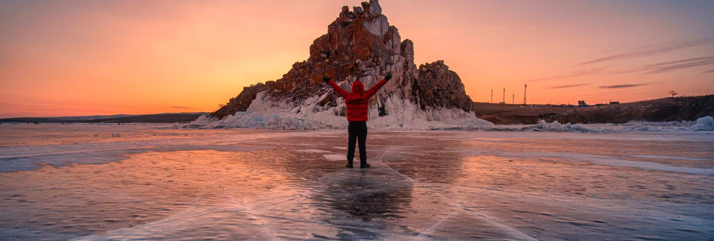 Traveler man wear red clothes and raising arm standing on natural breaking ice in frozen water at sunrise in lake baikal, siberia, russia.