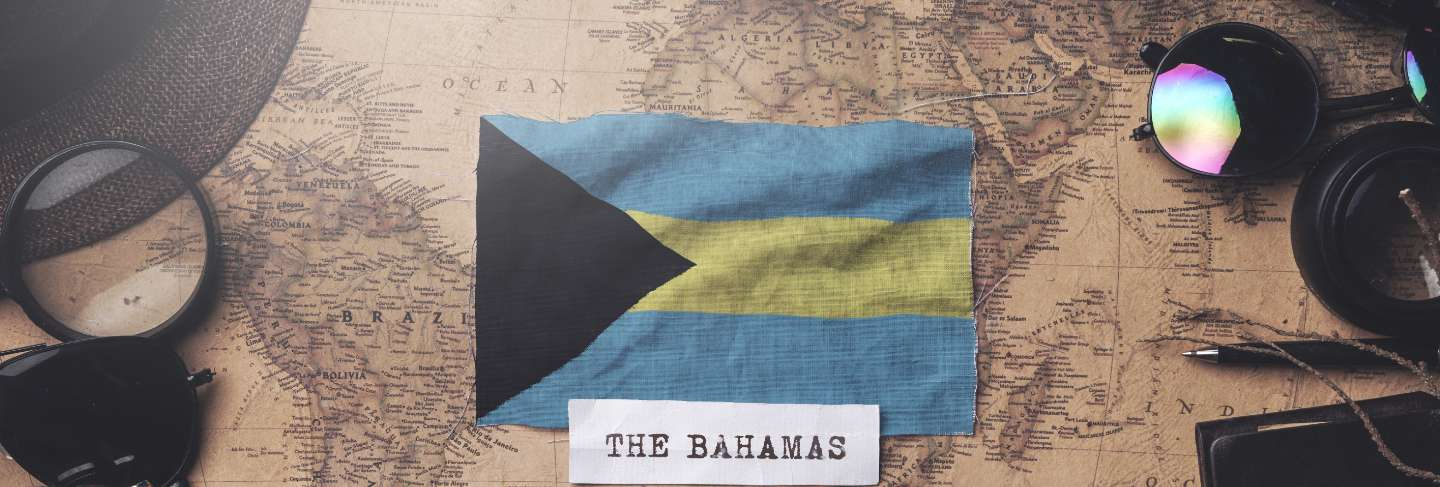 The bahamas flag between traveler's accessories on old vintage map. overhead shot