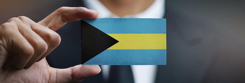 Businessman holding card of the bahamas flag