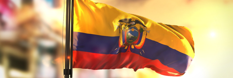 Ecuador flag against city blurred background at sunrise backlight