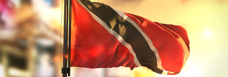 Trinidad and tobago flag against city blurred background at sunrise backlight
