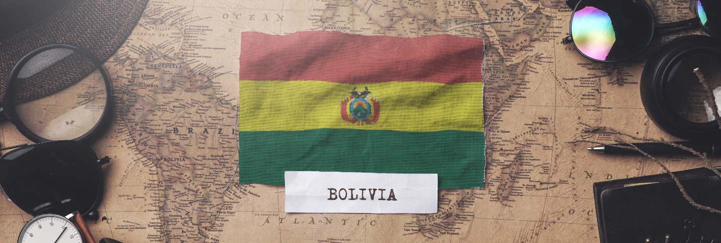 Bolivia flag between traveler's accessories on old vintage map.