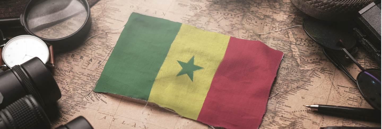 Senegal flag between traveler's accessories on old vintage map. tourist destination concept.