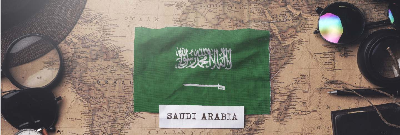 Saudi arabia flag between traveler's accessories on old vintage map. overhead shot
