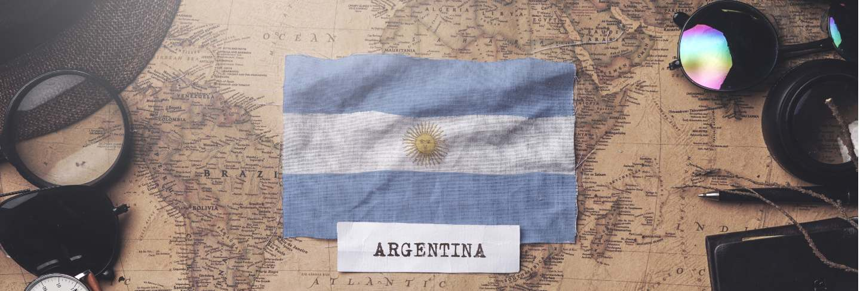 Argentina flag between traveler's accessories on old vintage map. overhead shot
