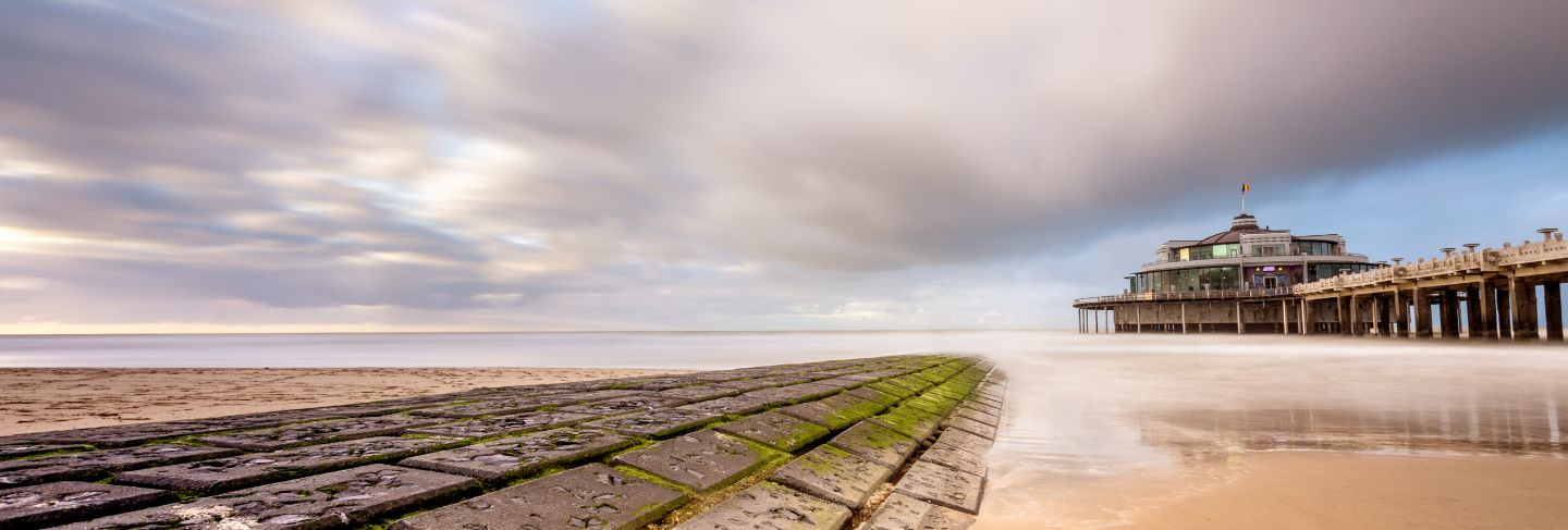 The palace pier at blankberg (belgium) on the fascinating north sea with dark clouds.