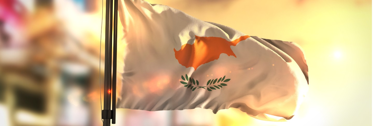 Cyprus flag against city blurred background at sunrise backlight