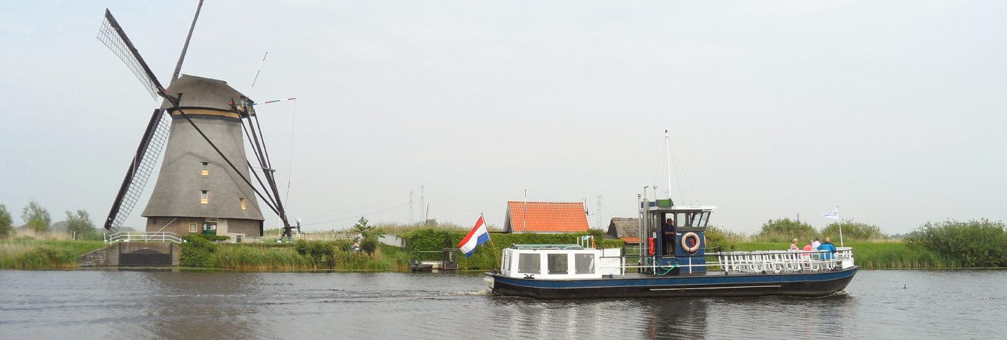 Traditional dutch windmill and boat on the canal at kinderdijk, molenwaard, netherlands