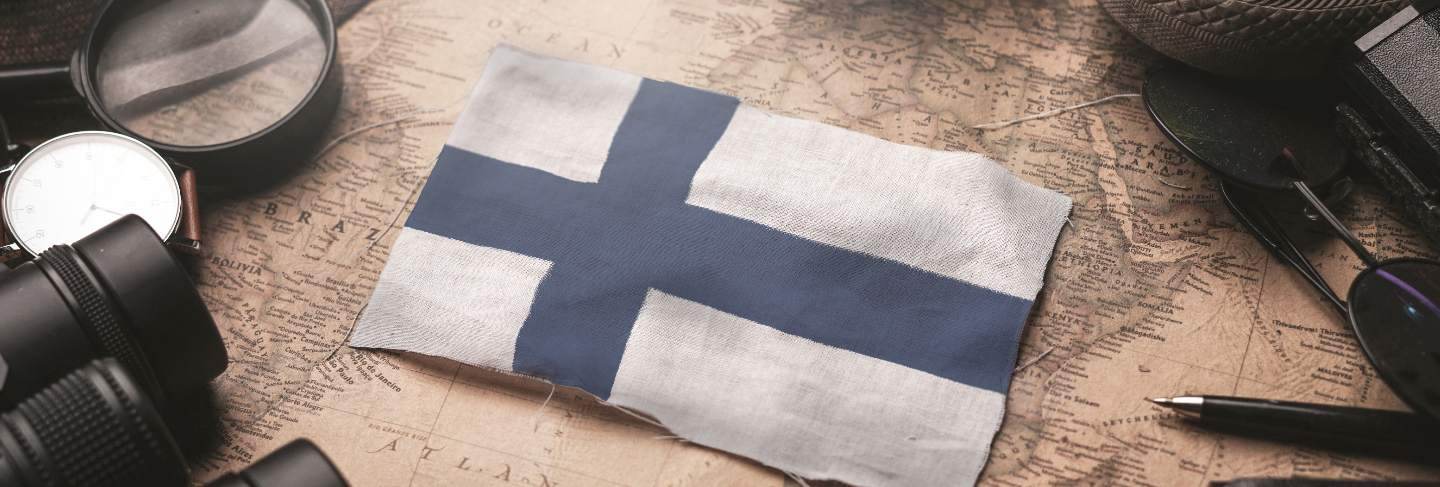 Finland flag between traveler's accessories on old vintage map. tourist destination concept