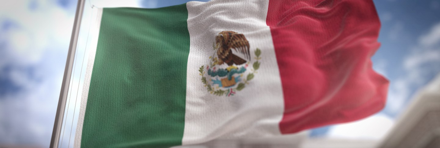 Mexico flag 3d rendering on blue sky building background