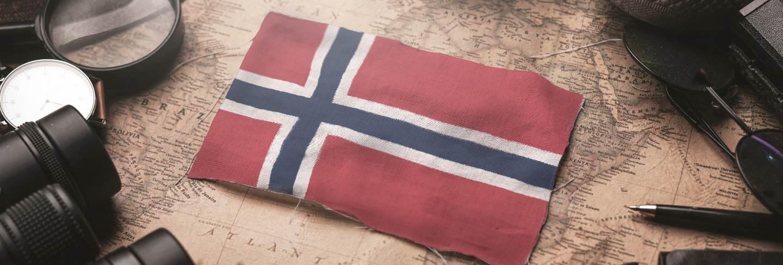 Norway flag between traveler's accessories on old vintage map. tourist destination concept