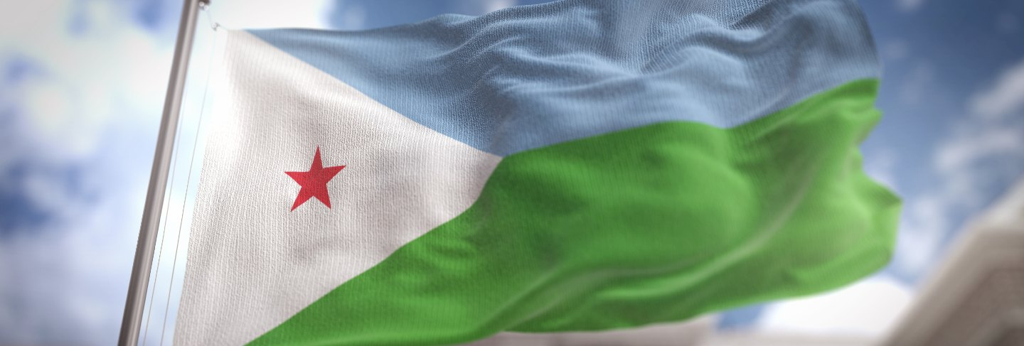 Djibouti flag against city blurred background at sunrise