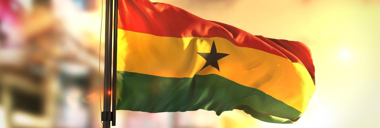 Ghana flag against city blurred background at sunrise backlight