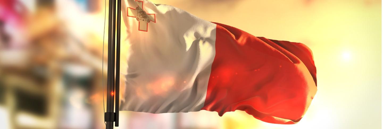 Malta flag against city blurred background at sunrise backlight