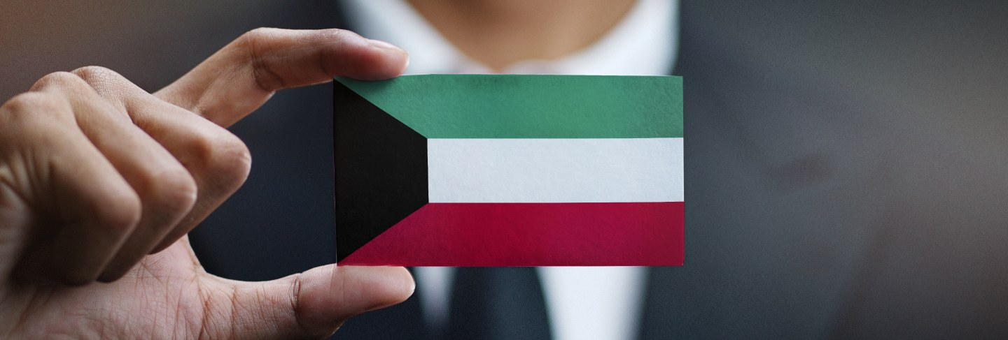 Businessman holding card of kuwait flag