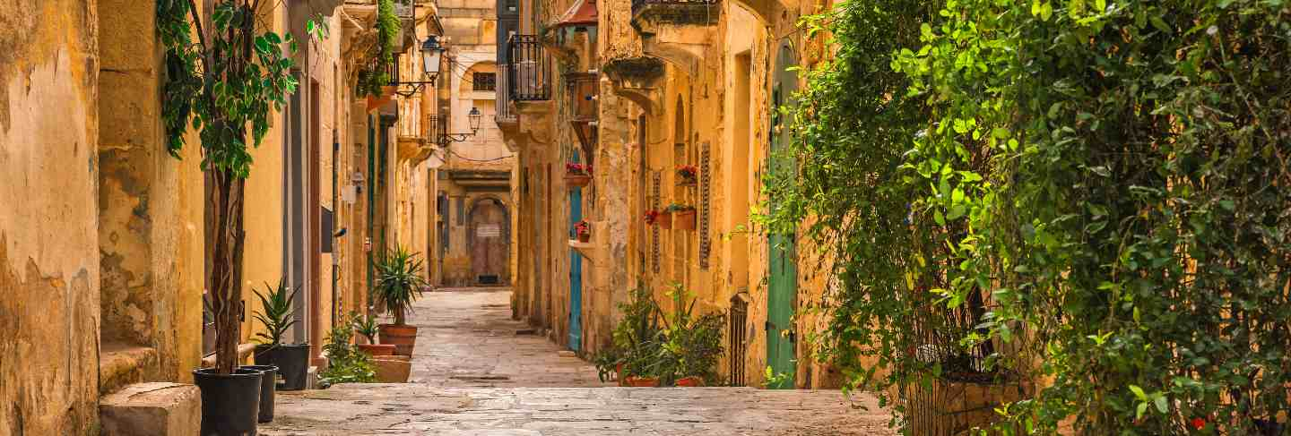Valletta, malta. old medieval empty street with yellow buildings and flower pots Premium Photo