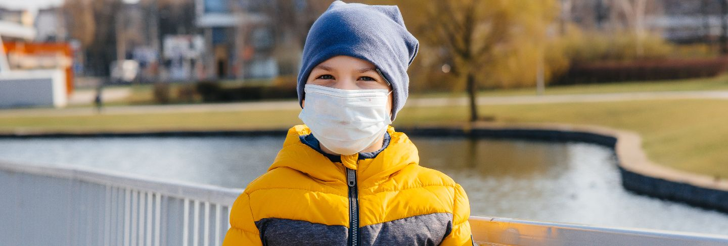 A boy stands on a gray background in a mask during a quarantine with free space. quarantine in the mask.