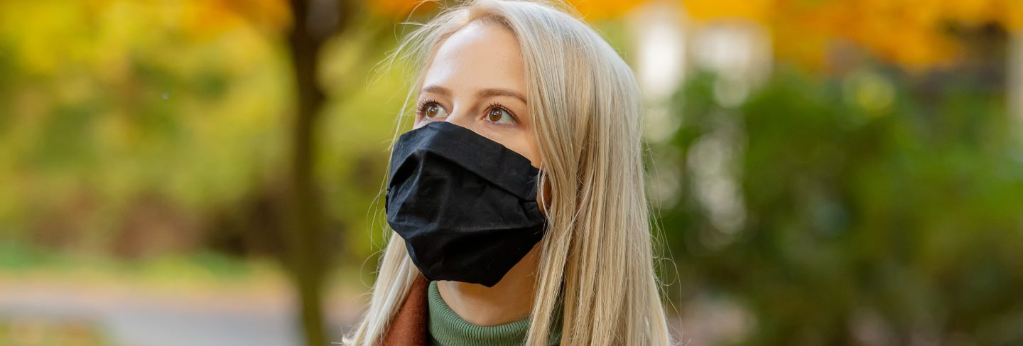 Style blonde in face mask and coat on autumn park with maples
