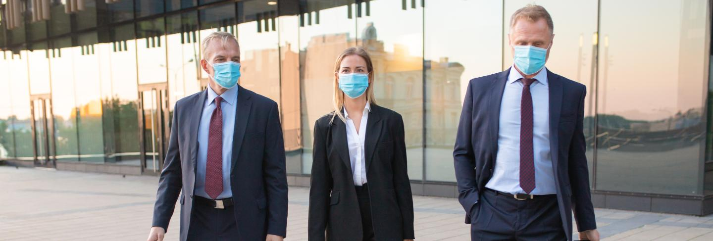 Business tourists in face masks visiting foreign partner office, wheeling suitcase, walking outdoors. front view. business trip and epidemic concept