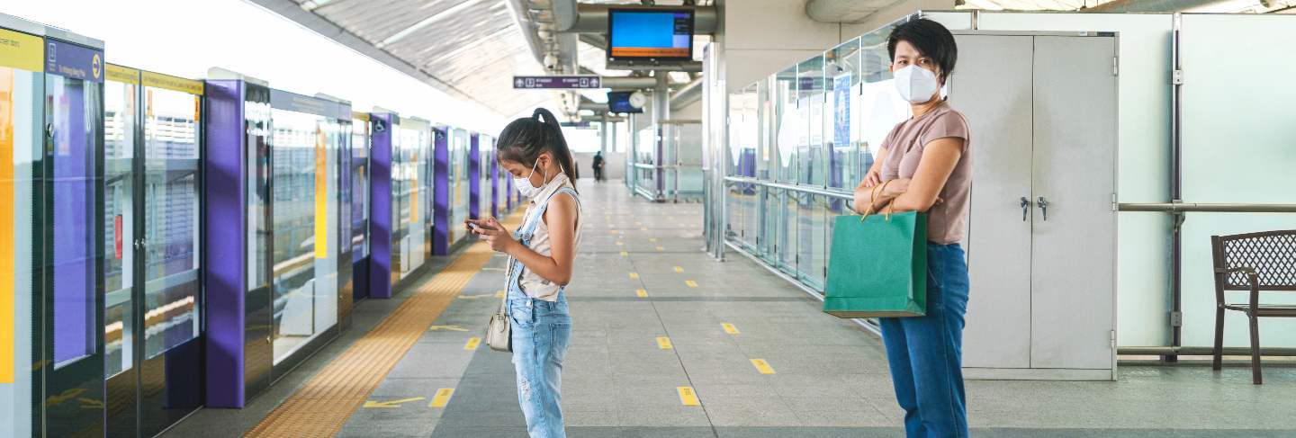 Asian woman keep distance to other people in empty subway platform