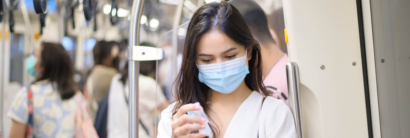 A young woman wearing protective mask in subway is using alcohol to wash hands, travel under covid-19 pandemic, safety travels, social distancing protocol